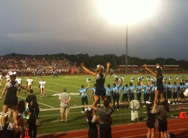 The football team and cheerleaders wait for the kick off of the first home game of the 2014 football season.