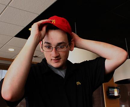 "Sophomore Anthony Tellez puts his hat on to go back to work after break. He works at McDonalds for extra spending money. "" [My job] can interfere with my grades,"" he said"
