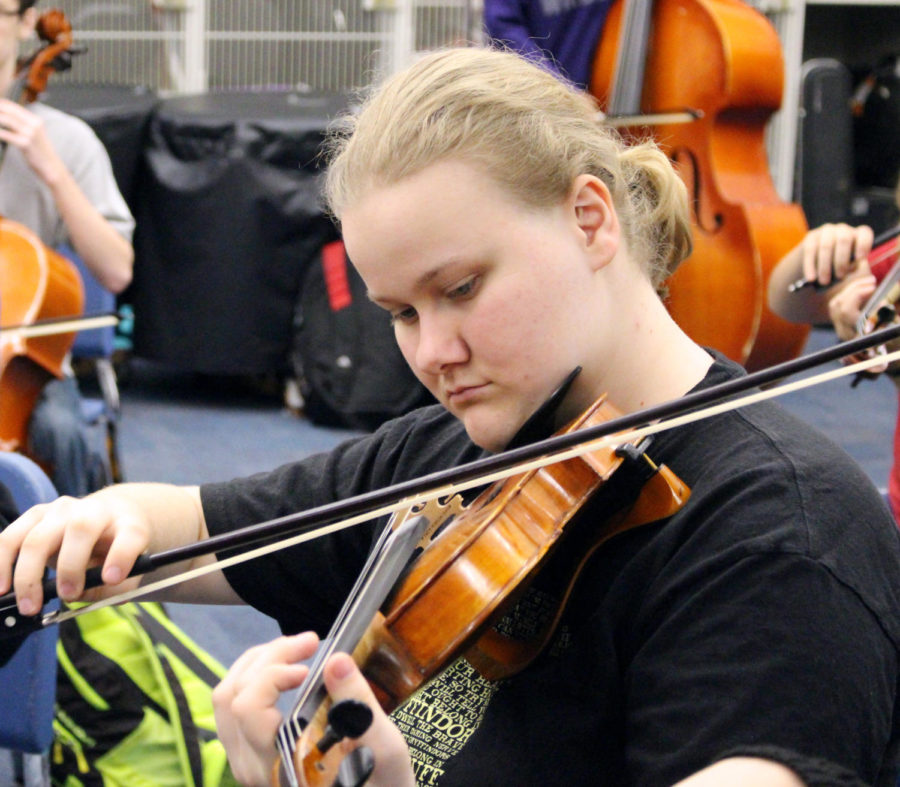 Junior Lindsey Wood warms up her violin prepping for the start of rehearsal. Wood first began with making sure her instrument was in tune then continued with running parts of her warm up book.