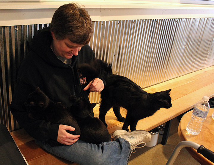 Customer Denise Nance relaxes with two kittens in her lap.