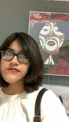 Senior Ivonee Morales-Mejia attends the North Kansas City School District art exhibit at Gladstone Community Center on Thursday, March 12. She stands with her piece 'Carmen,' which was chosen to represent Oak Park High School in the exhibit.
