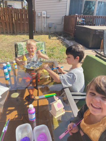 ernathy's grandchildren sitting at a table, doing fun activities such as painting. They're in Abernathy's backyard.